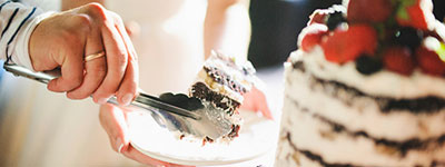 Bride and Groom cutting and plating their wedding cake